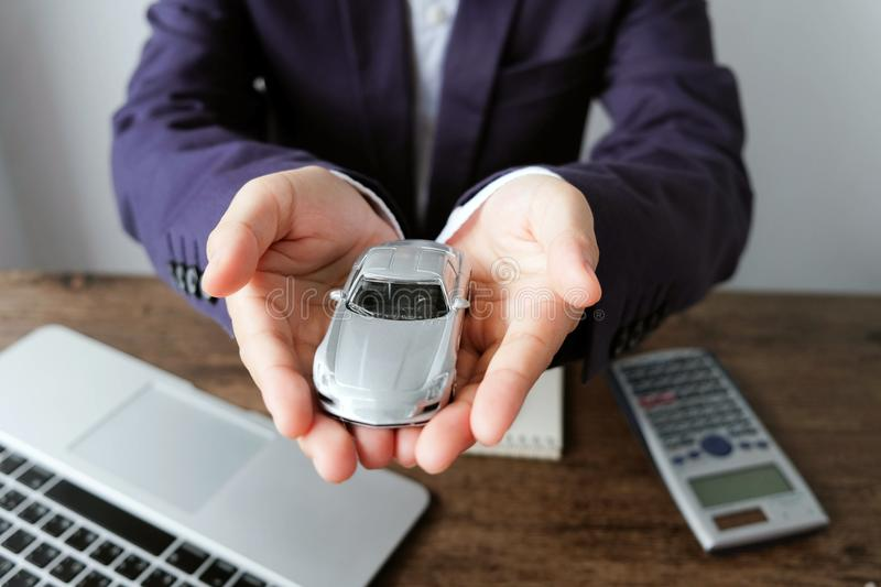 Miniature car model on hand with laptop and calculator on wooden royalty free stock image