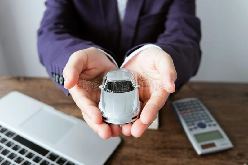 Miniature car model on hand with laptop and calculator on wooden royalty free stock photography