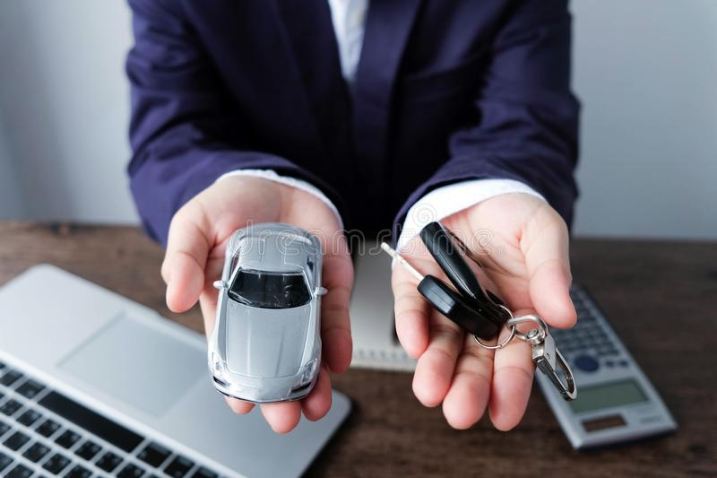 Miniature car model and key on hand with laptop and calculator o royalty free stock image