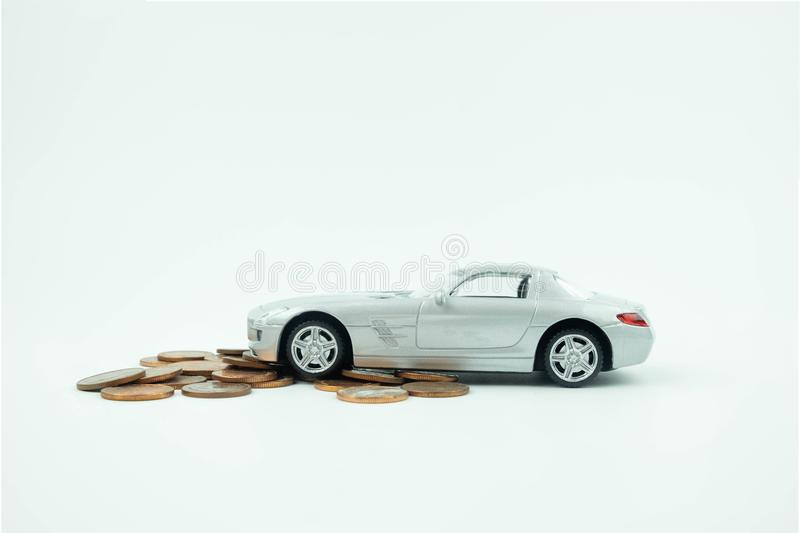 Miniature car model on a pile of coin on white background, Buying a car, car loan. royalty free stock images