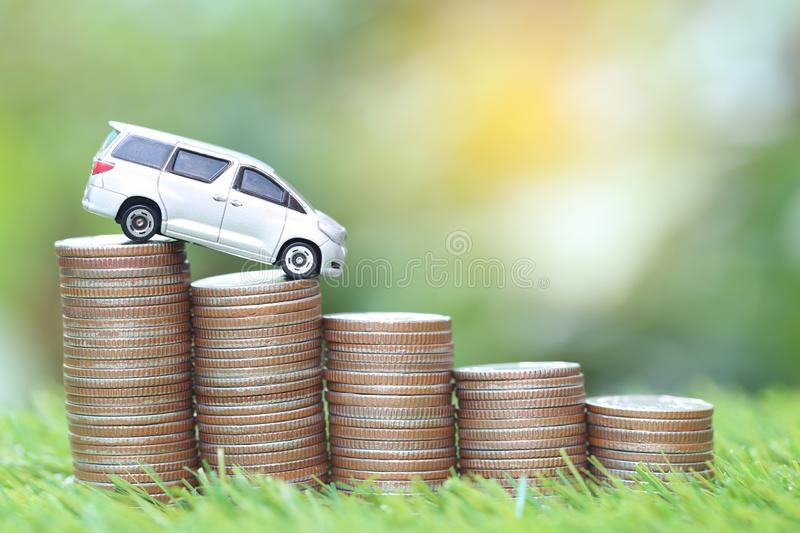 Miniature car model on stack of coins money on nature green background, Saving money for car, Finance and car loan, Investment and. Business concept stock photos