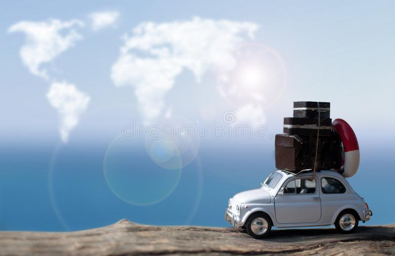Miniature car traveling, atlas world clouds stock image