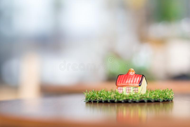Miniature ceramic house on wooden mock up over blurred green garden on day noon light. Image for property real estate investment concept stock photo