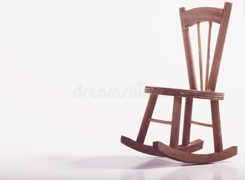 Miniature chair on wooden floor expressing lonely feeling and missing someone concept. Negative space for text royalty free stock image