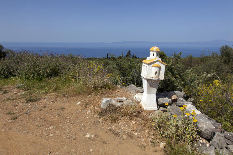 Miniature chapel on roadside in mani part of peloponnese in greece with blue sea in the background. Miniature chapel on roadside in mani part of peloponnese in royalty free stock photos