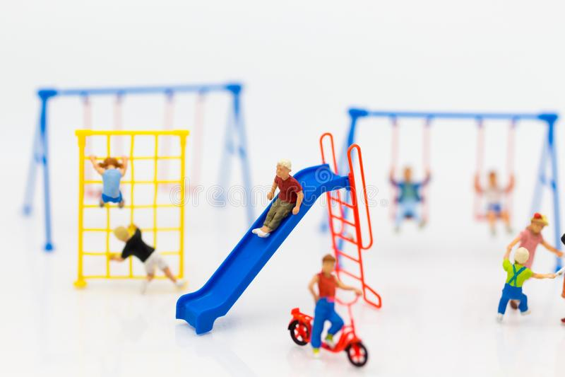 Miniature children: The boy is playing slider happily with friend on playground. Image use for Children`s Day. Miniature children: The boy is playing slider royalty free stock photos
