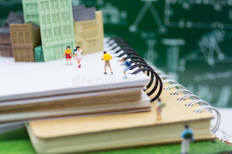 Miniature children : Group of children walking on books. Image use for taking a trip to school, education concept stock photo