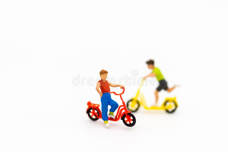 Miniature children: Two Boys cycling on white floor . Image use for Children`s day.  royalty free stock photos