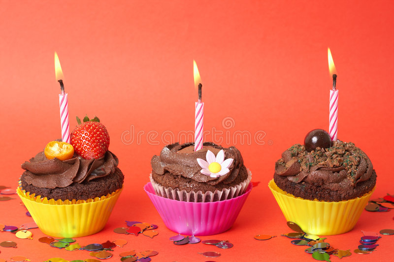 Miniature chocolate cupcakes with candles royalty free stock image