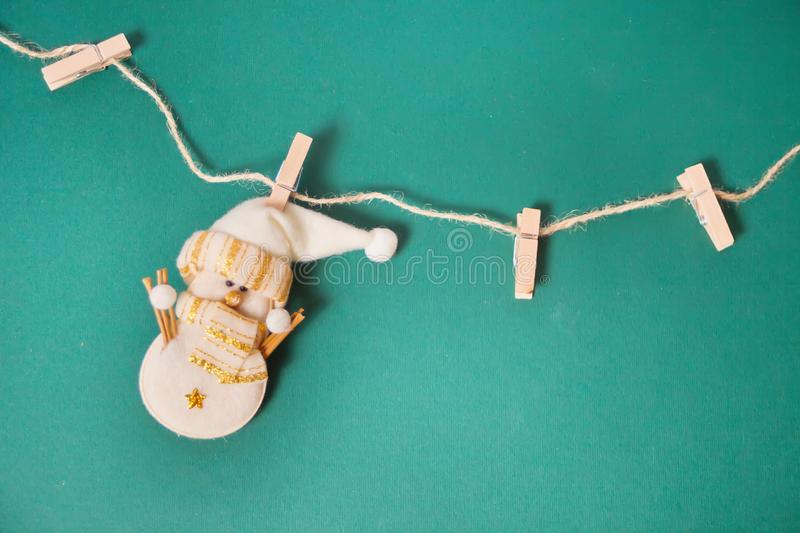 Miniature Christmas funny toy snowman hanging on the clothes pin on a green background royalty free stock image