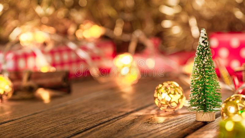 Miniature Christmas tree with blurred red  gift box background on wood table with copy space. Christmas, New Year, Valentine or royalty free stock photo