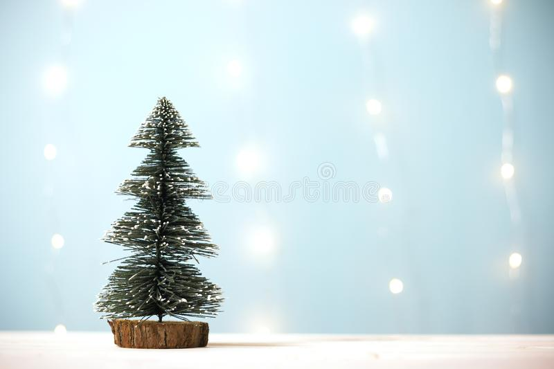 Miniature christmas tree on wooden table over blur bokeh light blue background stock photos