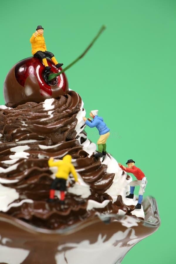 Miniature climbers on an ice cream sundae stock photography