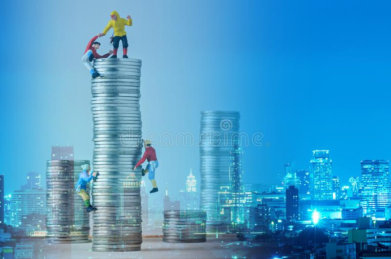 Miniature climbers team climbing on stack of coins stock images