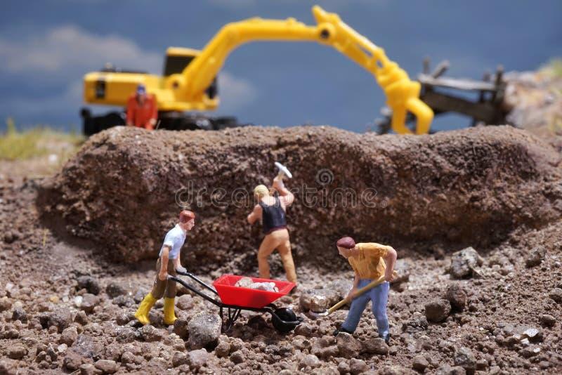 MiniatureContruction arbetare som arbetar lyftande stenen genom att använda skyffeln royaltyfria foton