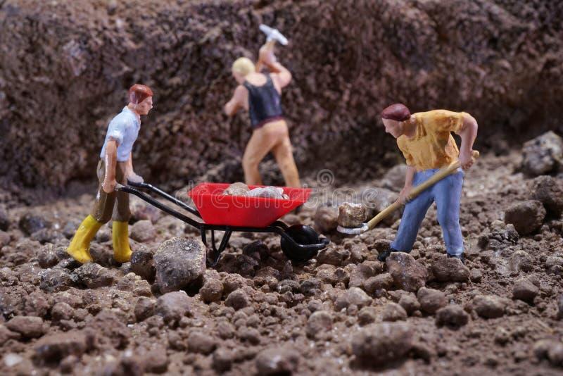 MiniatureContruction arbetare som arbetar lyftande stenen genom att använda skyffeln fotografering för bildbyråer