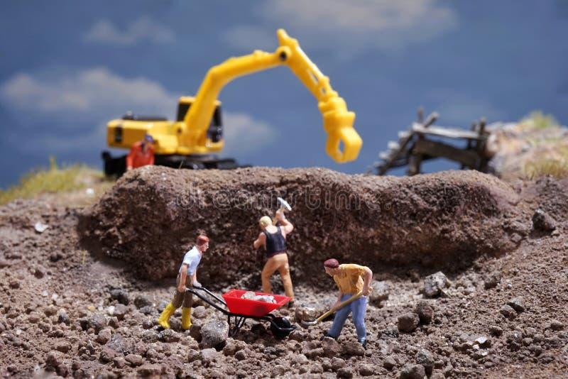 MiniatureContruction pracownicy pracuje podnośną kamienną używa łopatę obrazy royalty free