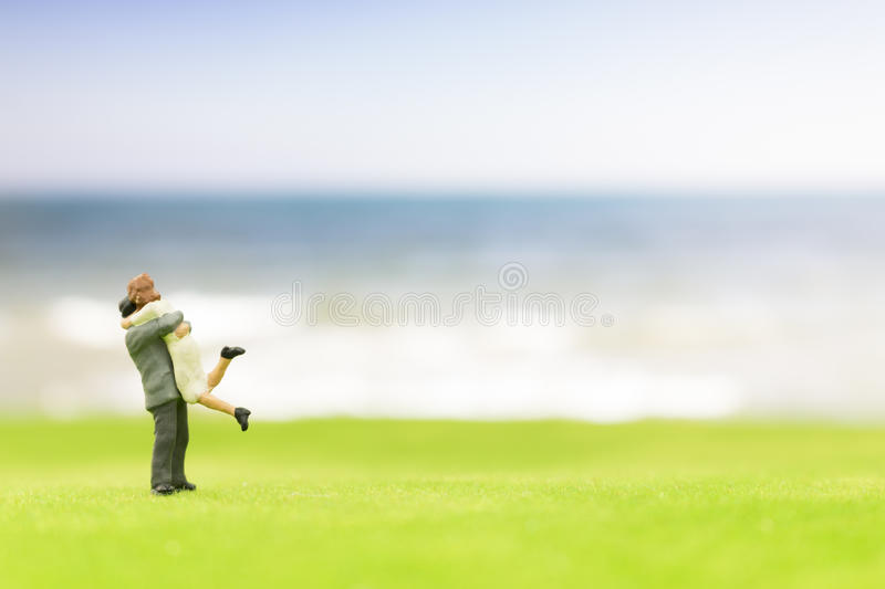Miniature couple on the beach. Background stock photography
