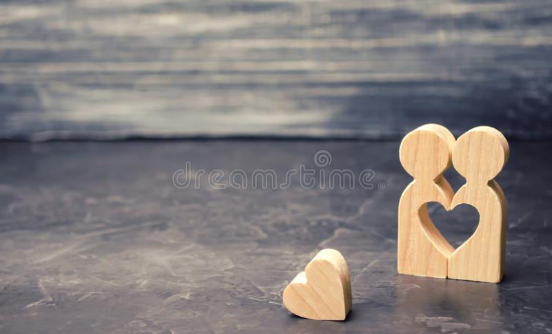 A miniature couple in love and a heart near them. The concept of family problems and loss of feelings for your loved one. royalty free stock image