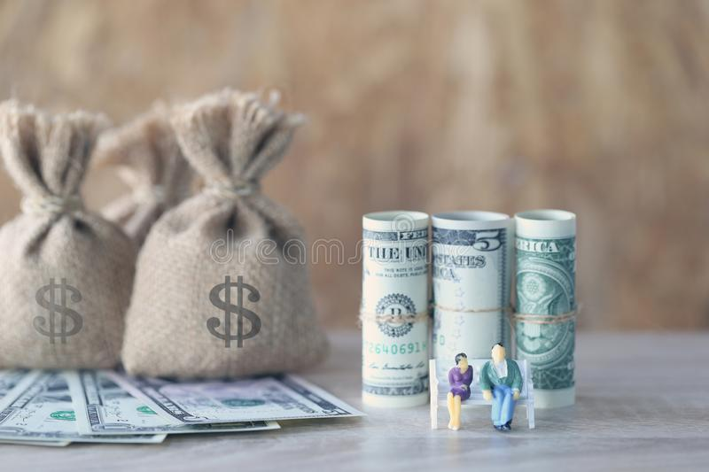 Miniature couple standing on the chair and money bag with banknote on wooden background, Save money for prepare in future and royalty free stock images
