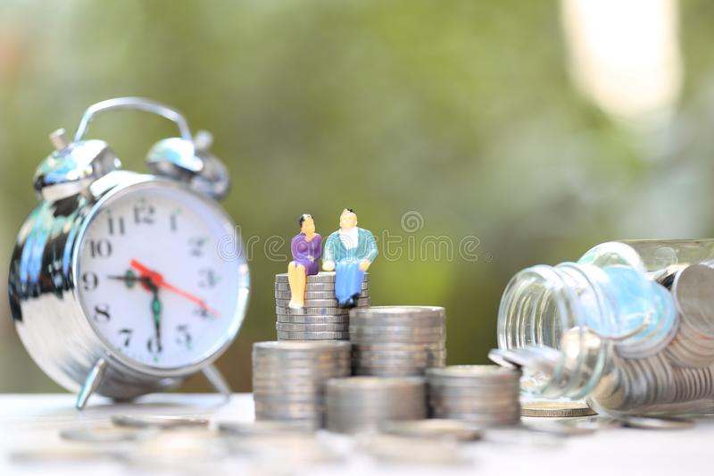 Miniature couple standing on coins money and glass bottle with alrm clock on natural green background, Save money for prepare in royalty free stock images