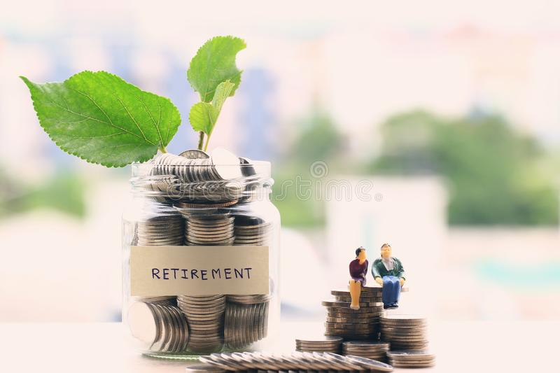 Miniature couple standing on coins money and glass bottle on city background, Save money for prepare in the future and retirement stock photography