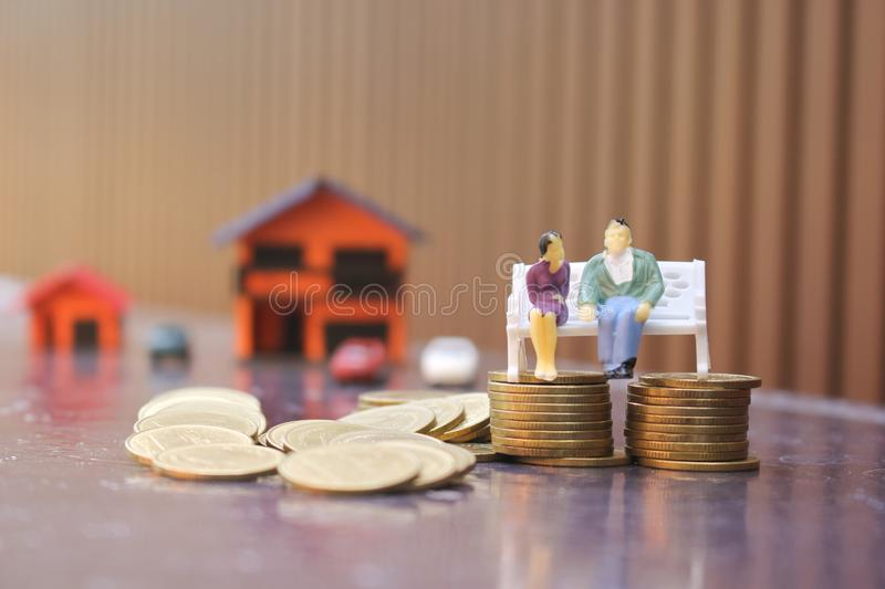 Miniature couple standing on coins money and glass bottle on city background, Save money for prepare in the future and retirement royalty free stock photo