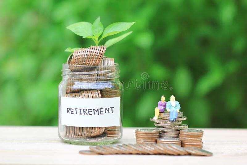 Miniature couple standing on coins money and glass bottle on city background, Save money for prepare in future and retirement. Concept stock image
