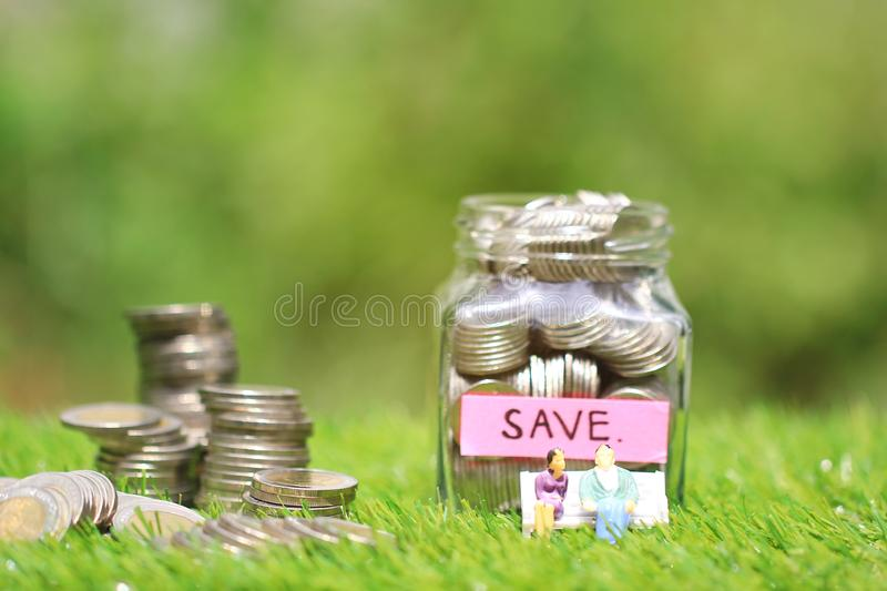Miniature couple standing on coins money with glass bottle on natural green background, Save money for prepare in future and royalty free stock image