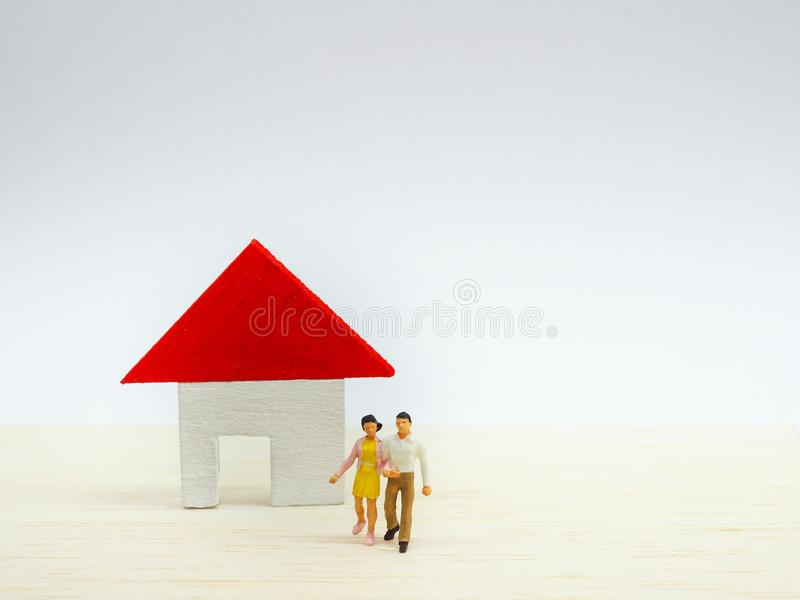 Miniature couple standing in front of small house on wooden back stock photo