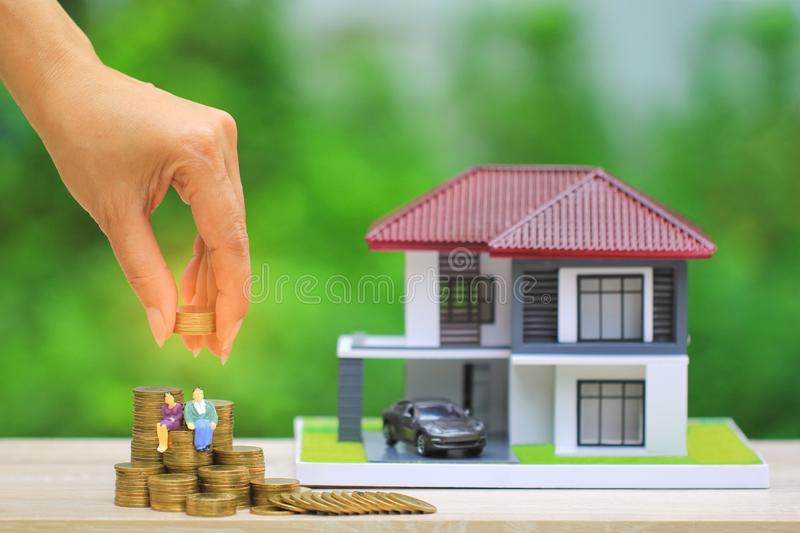 Miniature couple standing on gold coins money with model house and car on natural green background, Save money for prepare in stock photos