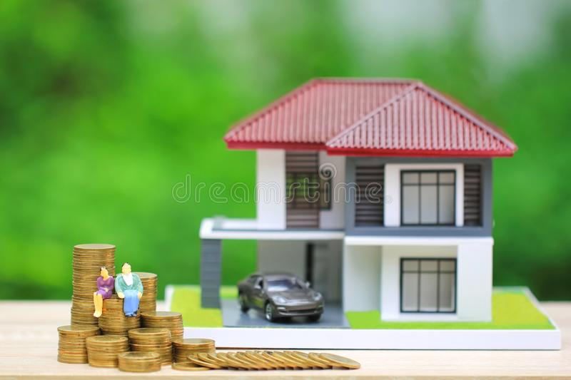 Miniature couple standing on gold coins money with model house and car on natural green background, Save money for prepare in royalty free stock image