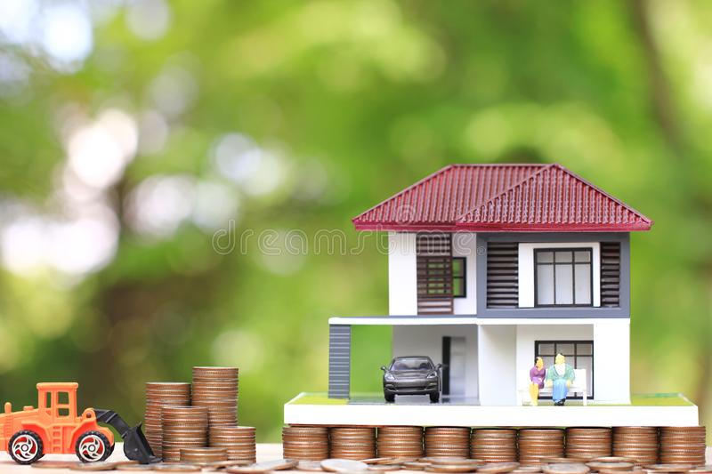 Miniature couple standing on model house and stack of coins money with truck toy on natural green background, Save money for. Prepare in future and retirement stock photos