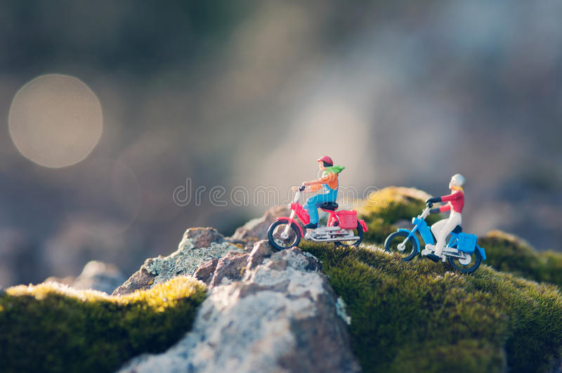 Miniature couple traveling through the countryside on vintage motorcycles at dawn royalty free stock images