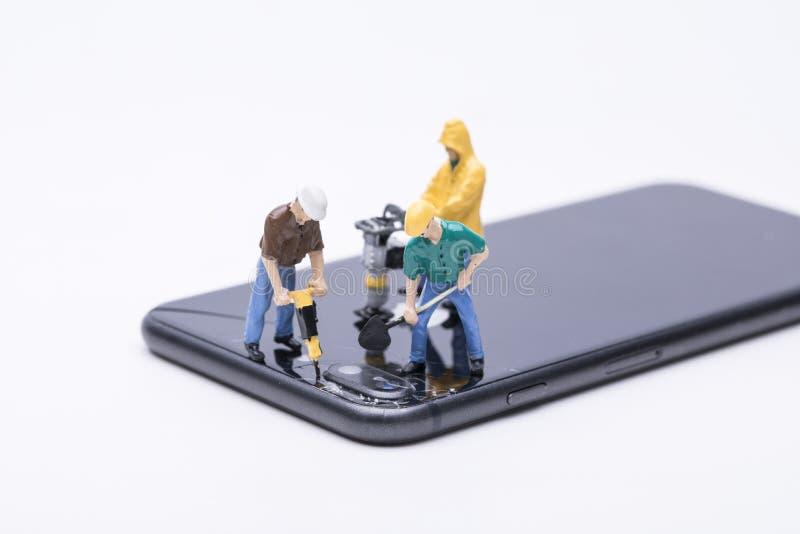 Miniature d'ouvrier chargé de l'entretien réparant le téléphone photo stock