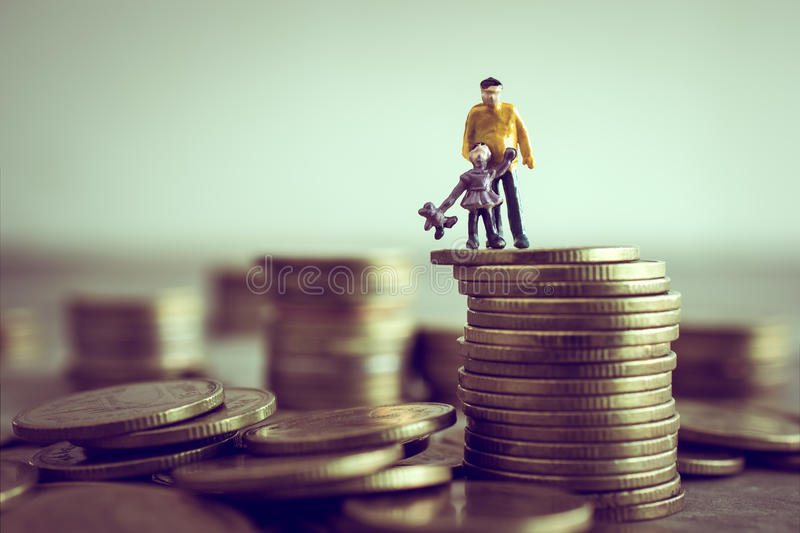 Miniature Dad and Kids standing on top of the money save money c. Oncept royalty free stock photos