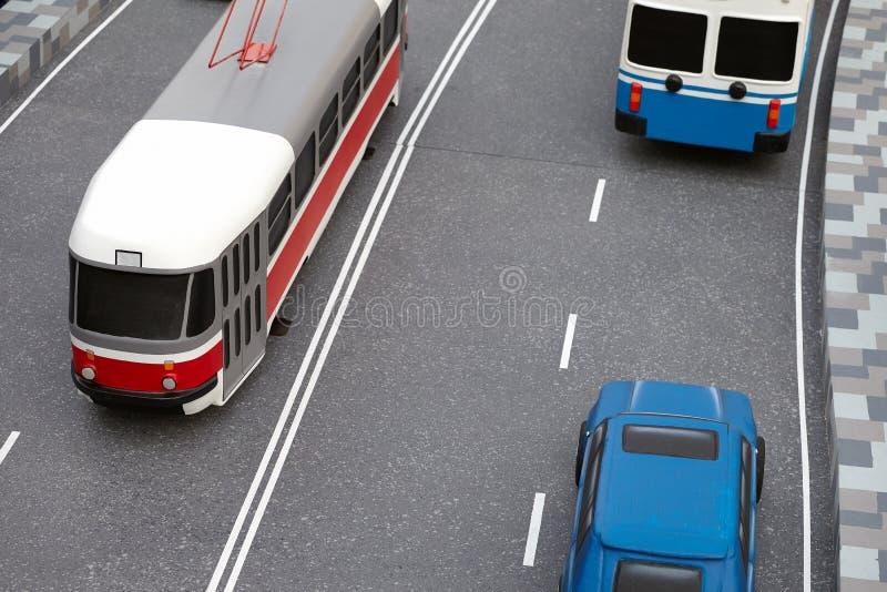 Miniature de circulation routière avec des modèles de jouet d'un tram, d'un autobus de chariot et d'une voiture modernes image libre de droits