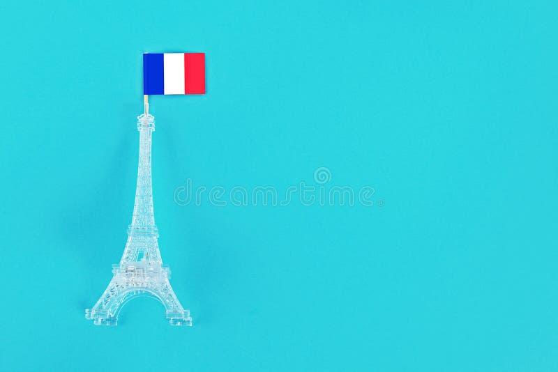 Miniature de Tour Eiffel avec un drapeau français sur un fond bleu Copiez l'espace Le concept des vacances est le 14 juillet, photographie stock