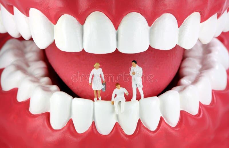 Miniature dentists on teeth