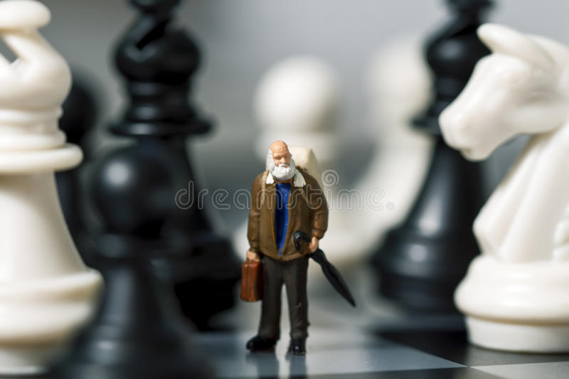 Miniature doll traveler and chess. Old traveler in chessboard royalty free stock images