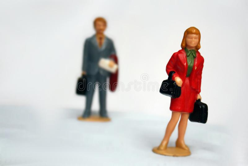 Miniature elegant woman and some man behind her, looking or follow the lady, stalking or sexual harassment concept, admirer, stock photos