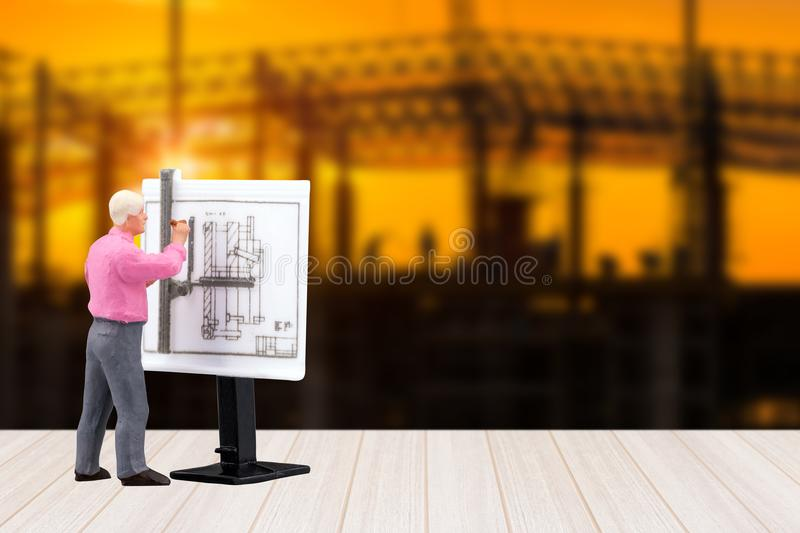 Miniature engineering people working on construction drawing. With construction site in background.Elegant Design for industrial and construction concept royalty free stock photography