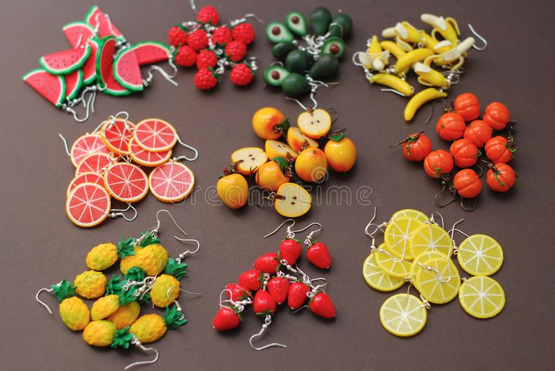 Miniature Fake Polymer Clay Fruits on Brown Background. , Polymer Clay Earrings, Plastic Summer Fruits stock photography