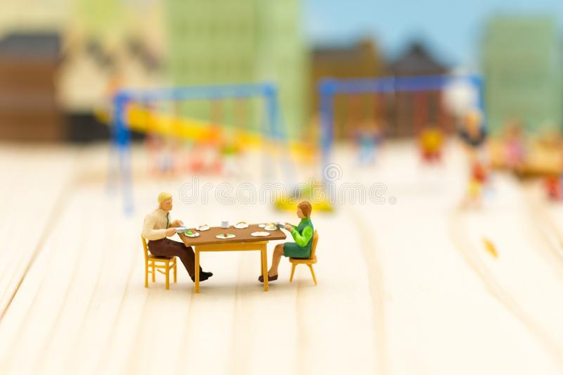 Miniature Families are celebrating , eating together happily. Us royalty free stock photo