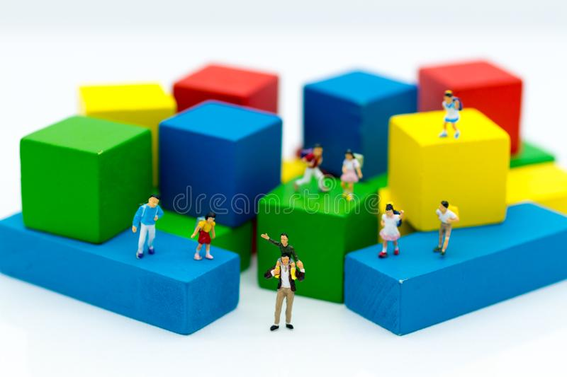 Miniature family: Father gave the son a ride on the neck and children stand around. Image use for expressed love stock photography