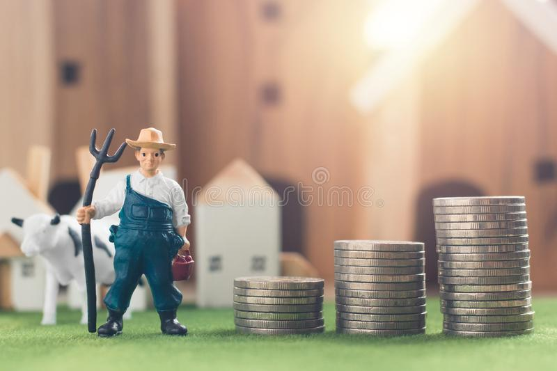 Miniature Farmer and cow figure model with money coin stack on Simulation grass. Wooden house in the background, agriculture and financial concept royalty free stock images