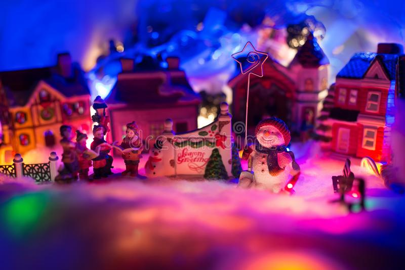 holiday greeting sign with snowman holding star stands kid choir in front of a christmas village. Fairytale miniature scenery royalty free stock images
