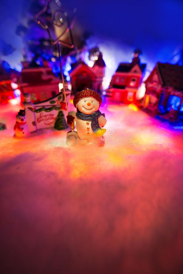 snowman holding star of bethlehem stands in front of a christmas village. Holidays miniature scenery stock photos