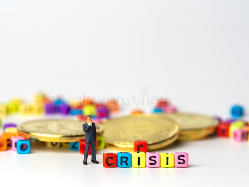 Miniature figure businessman in dark blue suit standing backside of colorful of CRISIS alphabet and golden coin and thinking of th royalty free stock image