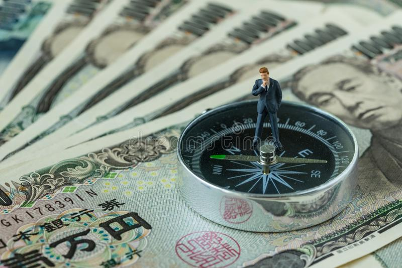 miniature figure businessman thinking standing on compass on pile of japanese yen banknotes as financial leader direction concept stock image